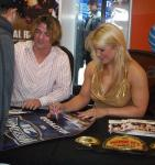 Beth Phoenix in a gold dress signing autographs.jpg
